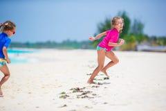 Meninas que têm o divertimento na praia tropical que joga junto na praia Fotos de Stock Royalty Free