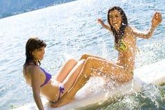 Meninas que têm o divertimento na prancha imagem de stock royalty free