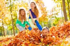 Meninas que têm o menino de arrasto do divertimento que coloca na terra Imagem de Stock