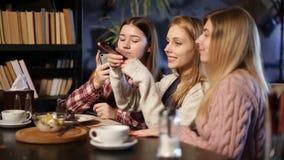 Meninas que tomam fotos da sobremesa com telefones celulares video estoque