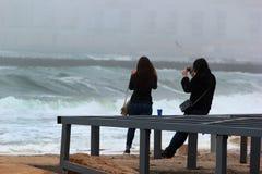 Meninas que tomam fotos de uma tempestade do mar Fotos de Stock