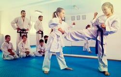 Meninas que treinam durante a classe do karaté imagem de stock royalty free