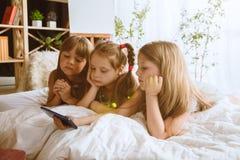 Meninas que usam dispositivos diferentes em casa imagens de stock royalty free
