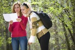 Meninas que verific um mapa Fotografia de Stock