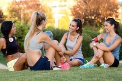 Meninas running que têm o divertimento no parque com telefone celular imagem de stock