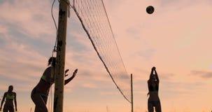 Meninas 'sexy' do voleibol no jogo do biquini na praia no voleibol do verão na areia no por do sol no movimento lento vídeos de arquivo