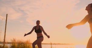 Meninas 'sexy' do voleibol no jogo do biquini na praia no voleibol do verão na areia no por do sol no movimento lento video estoque