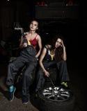 Meninas 'sexy' dos mecânicos cansados que sentam-se em uma pilha dos pneus em reparos de um carro e no fumo, uma das meninas que  Fotos de Stock Royalty Free