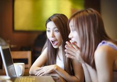Meninas surpreendidas que olham o portátil na cafetaria Foto de Stock Royalty Free