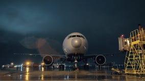 Mening aan de cockpit en de motoren van geparkeerd lijnvliegtuig in luchthaven bij nacht stock footage