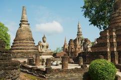 Mening aan het de ruïnes en standbeeld van zittingsboedha bij Wat Mahathat-tempel in het Historische Park van Sukhothai, Thailand Stock Afbeelding