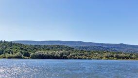 Mening aan rivier met bezinningen en blauwe bewolkte hemel stock foto's
