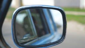Mening aan zijspiegel van oude retro auto met vage stad bij achtergrond Het uitstekende automobiele drijven bij de stadsstraat  stock videobeelden