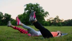 Mening av dina absflickor Grupp av ungt idrotts- folk i sportswearen som gör fysiska övningar på grönt gräs i sommar
