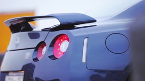 Mening bij bumper van nieuwe donkerblauwe auto op parkeren presentatie Rood lichten auto Koude schaduwen stock video