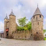 Mening bij de muur en de oude poort Helpoort aan Maastricht - Nederland stock foto