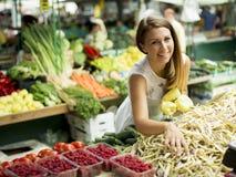 Mening bij jonge vrouw het kopen groenten bij de markt Stock Foto