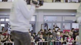 Mening bij publiek op tribune op de concurrentie in skatepark cameraman Achter omheining menigten teens stock video
