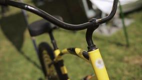 Mening bij zwarte en gele creatieve fiets die op groen gras blijven De zomerfestival Interiortransportation van de leiding wheel stock video