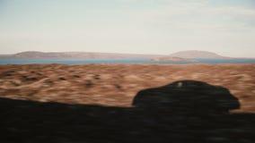 Mening binnen de auto van mooi zonsonderganglandschap van bergen en water, meer Mening van de voertuigschaduw buiten Stock Foto's
