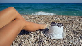 Mening die van de benen van de mooie vrouw op het strand dichtbij het overzees, tijdens de zomerweekend ontspannen die van goede  stock videobeelden