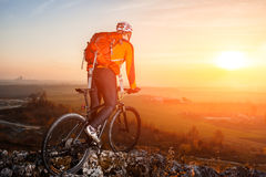 Mening die van fietser zich met bergfiets op heuvelsleep bij zonsondergang bevinden Royalty-vrije Stock Foto