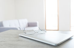 Mening die van glazen op moderne laptop met Skandinavisch ontwerpbinnenland liggen stock afbeeldingen