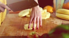Mening die van vrouwenhanden ananas snijden in stukken stock videobeelden
