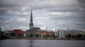 Mening door de Daugava-Rivier van de Kerk van Heilige Peter ` s tegen de achtergrond van de bewolkte hemel Riga Letland, stock video