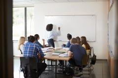Mening door Deuropening van de Wiskundeklasse van At Whiteboard Teaching van de Middelbare schoolprivé-leraar stock afbeelding