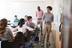Mening door Deuropening van Middelbare schoolleerling het Schrijven op Whiteboard in Klasse stock foto