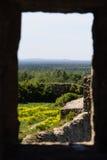 Mening door het venster in de muur van een geruïneerde steenvesting Koporye Stock Foto