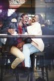 Mening door koffievenster van een jonge gelukkige donkere gevilde man en een vrouw die pret hebben terwijl het zitten samen in ba royalty-vrije stock foto's