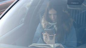 Mening door windscherm van de auto op jonge donkerbruine vrouw die in blauw benedenjasje de telefoon bekijken stock video