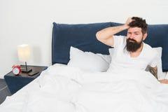 Mening evakuerat efter dagarbete energi och tr?tthet sovande och vaket mogen man med sk?gget i pajama p? s?ng arkivbilder