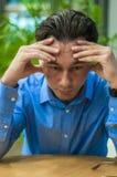 Mening evakuerat Frustrerad ung man som håller ögon stängda, medan sitta på hans arbetsplats arkivfoton
