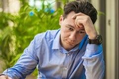 Mening evakuerat Frustrerad ung man som håller ögon stängda, medan sitta på hans arbetsplats i regeringsställning royaltyfria foton