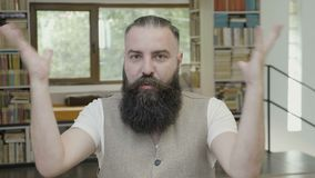 Mening geblazen reactie van een jonge aantrekkelijke bedrijfsmens met baardzitting in het bureau - stock footage