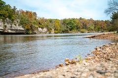 Mening naast een rivier met dalingsbomen stock afbeelding