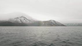 Mening over berg met sneeuwpieken en overzees Overzees schip die voorbij sneeuwberg varen stock videobeelden