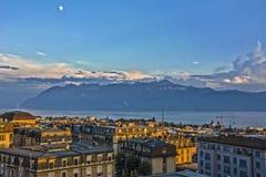 Mening over de daken van Lausanne bij zonsondergang met meer Genève en Alpen Stock Foto's