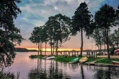 Mening over de meer visserijhaven met boten op de kust tijdens zonsondergang worden geparkeerd die royalty-vrije stock foto