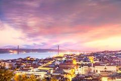 Mening over de stad van Lissabon en 25 abrilbrug bij zonsondergang, Portugal Stock Foto's
