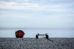 Mening over de Zwarte Zee met stenenstrand en gescheiden boot en aanhangwagen Stock Afbeeldingen