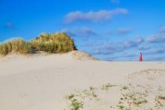 Mening over duinen op rode vuurtoren stock fotografie