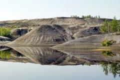 Mening over een overstroomde steengroeve met bezinning van heuvels stock fotografie