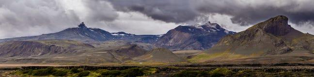 Mening over een reusachtig berg en een plattelandshuisje in IJsland met dramatische hemel royalty-vrije stock afbeelding