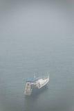 Mening over eenzaam boot en Meer Baikal onder de mist Stock Fotografie