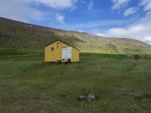 Mening over latrar kampeerterrein in adalvikinham met de gele cabine van de noodsituatieschuilplaats in het westenfjorden Hornstr stock afbeelding