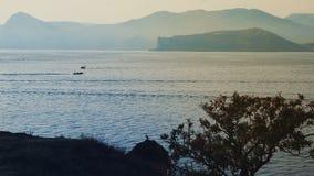 Mening over overzeese baai met bergen bij avond stock video
